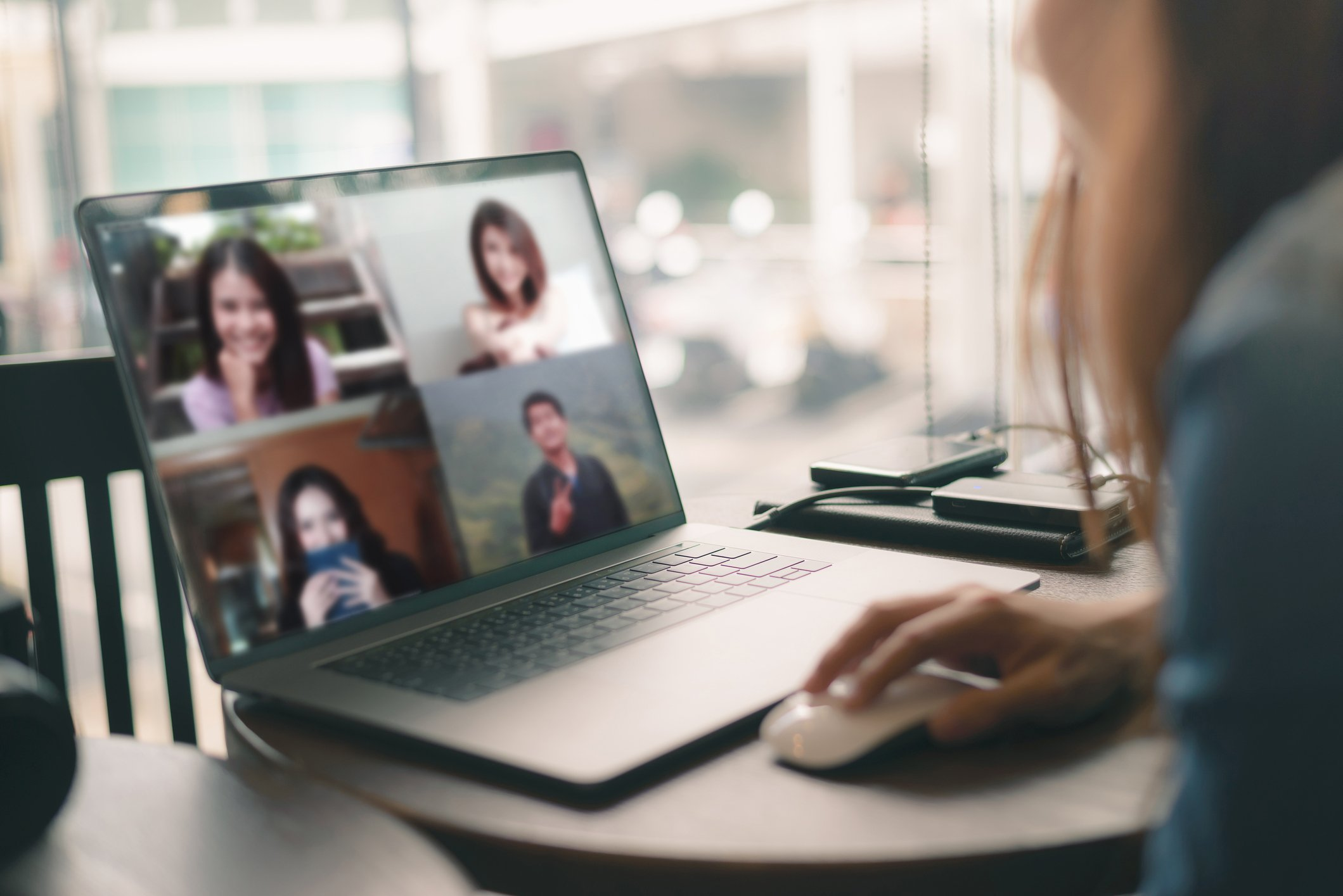 Young woman talking about freelancer report in video conference. Asian team using laptop and tablet online meeting in video call.Working from coffee shop , Working remotely and Social isolation.